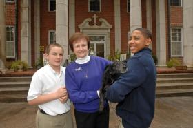 Sister Mary Alvin Seubott of Saint Mary's Home with two of her resident boys Royce, left, and Quevon, and their pet dog Millie. (Photo by John Carrington/Savannah Morning News)